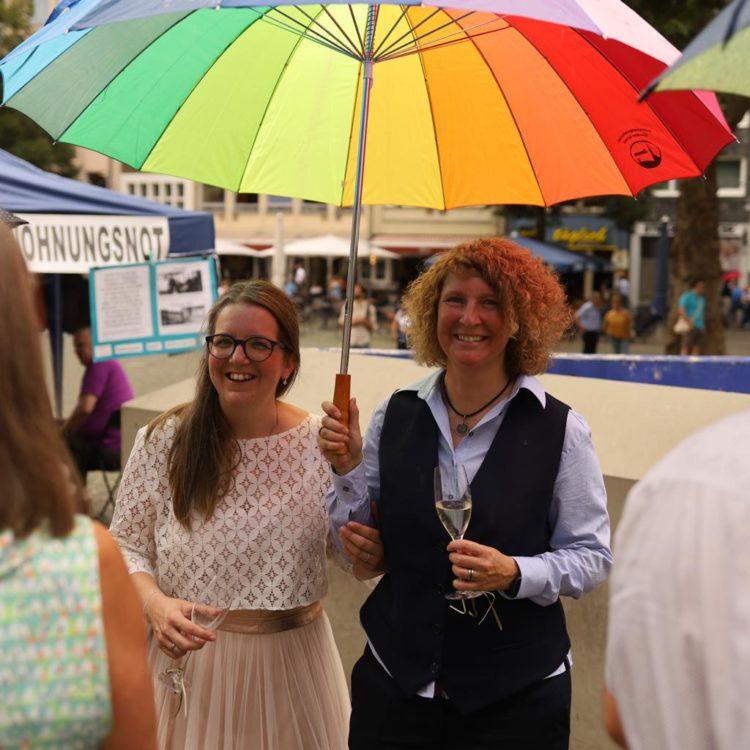 noni Brautmode, Brautpaar unter Regenbogenschirm zur Regenbogenhochzeit