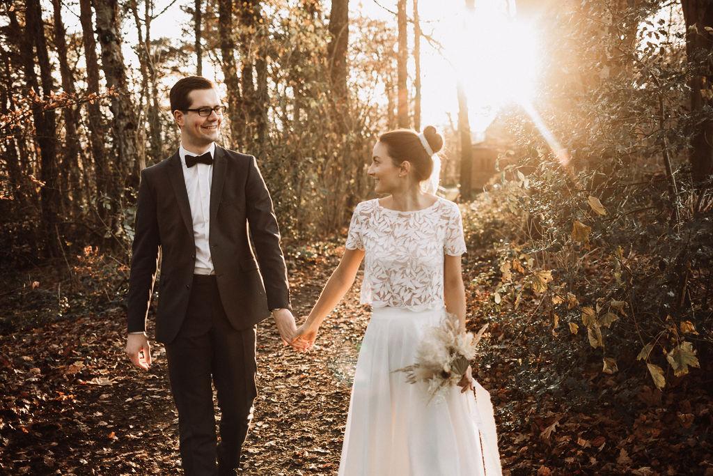 noni Brautmode, Hochzeitsshooting im Wald, Brautpaar händchenhaltend mit Sonneneinfall im Hintergrund. Bräutigam mit dunklem Anzug, Braut in Kurzarm-Kleid mit Boho-Spitze