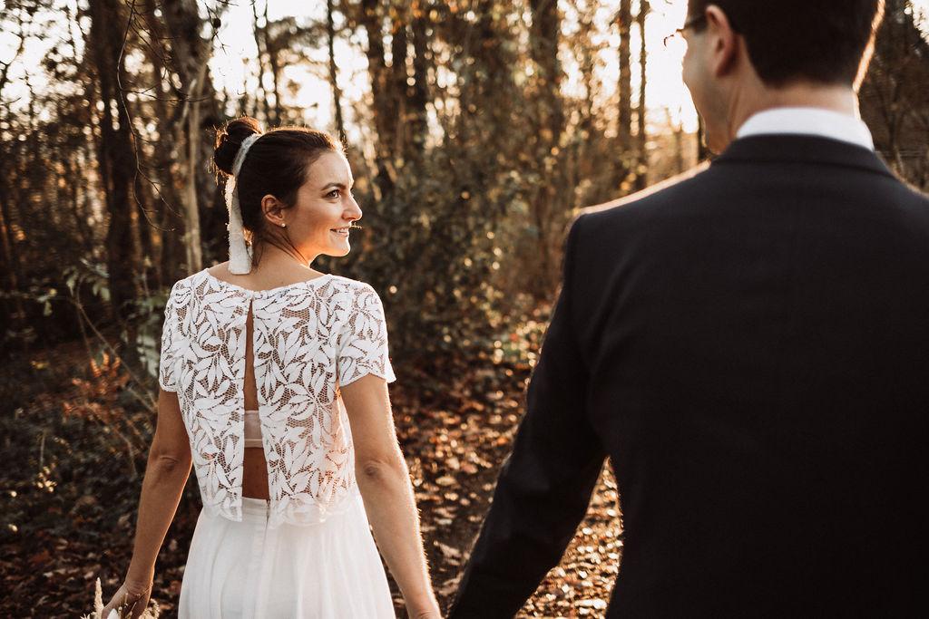 noni Brautmode, Hochzeitsshooting im Wald, Brautpaar händchenhaltend mit Sonneneinfall im Hintergrund. Bräutigam mit dunklem Anzug, Braut in Kurzarm-Kleid mit Boho-Spitze, händchenhaltend