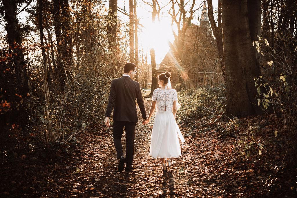 noni Brautmode, Hochzeitsshooting im Wald, Brautpaar händchenhaltend mit Sonneneinfall im Hintergrund. Bräutigam mit dunklem Anzug, Braut in Kurzarm-Kleid mit Boho-Spitze, händchenhaltend, Rückenansicht