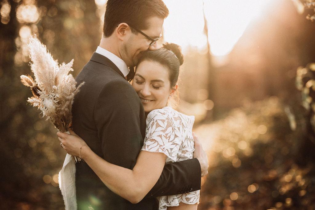 noni Brautmode, Hochzeitsshooting im Wald, Brautpaar händchenhaltend mit Sonneneinfall im Hintergrund. Bräutigam mit dunklem Anzug, Braut in Kurzarm-Kleid mit Boho-Spitze, sich umarmend