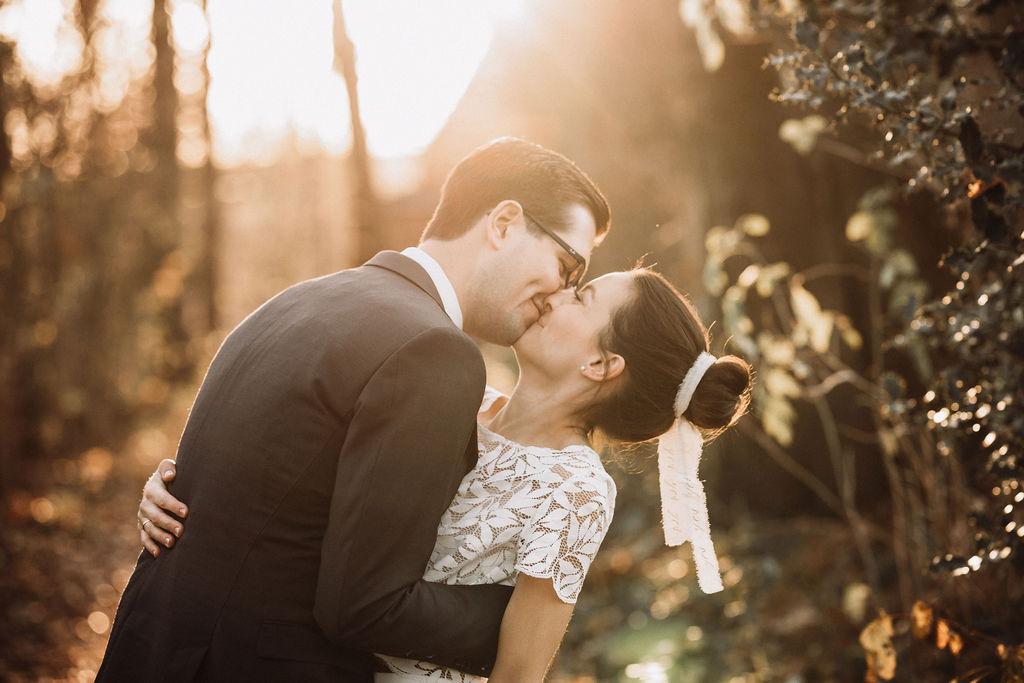 noni Brautmode, Hochzeitsshooting im Wald, Brautpaar händchenhaltend mit Sonneneinfall im Hintergrund. Bräutigam mit dunklem Anzug, Braut in Kurzarm-Kleid mit Boho-Spitze, küssend