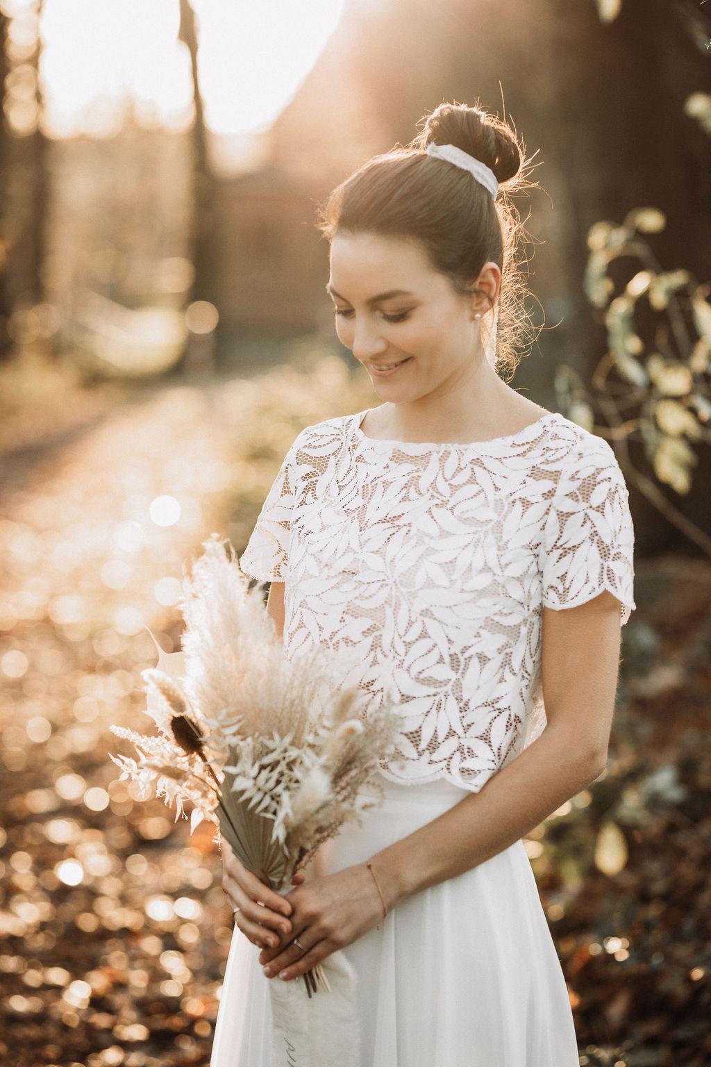 noni Brautmode, Hochzeitsshooting im Wald, Brautpaar händchenhaltend mit Sonneneinfall im Hintergrund. Braut in Kurzarm-Kleid mit Boho-Spitze und Trockenblumenstrauss
