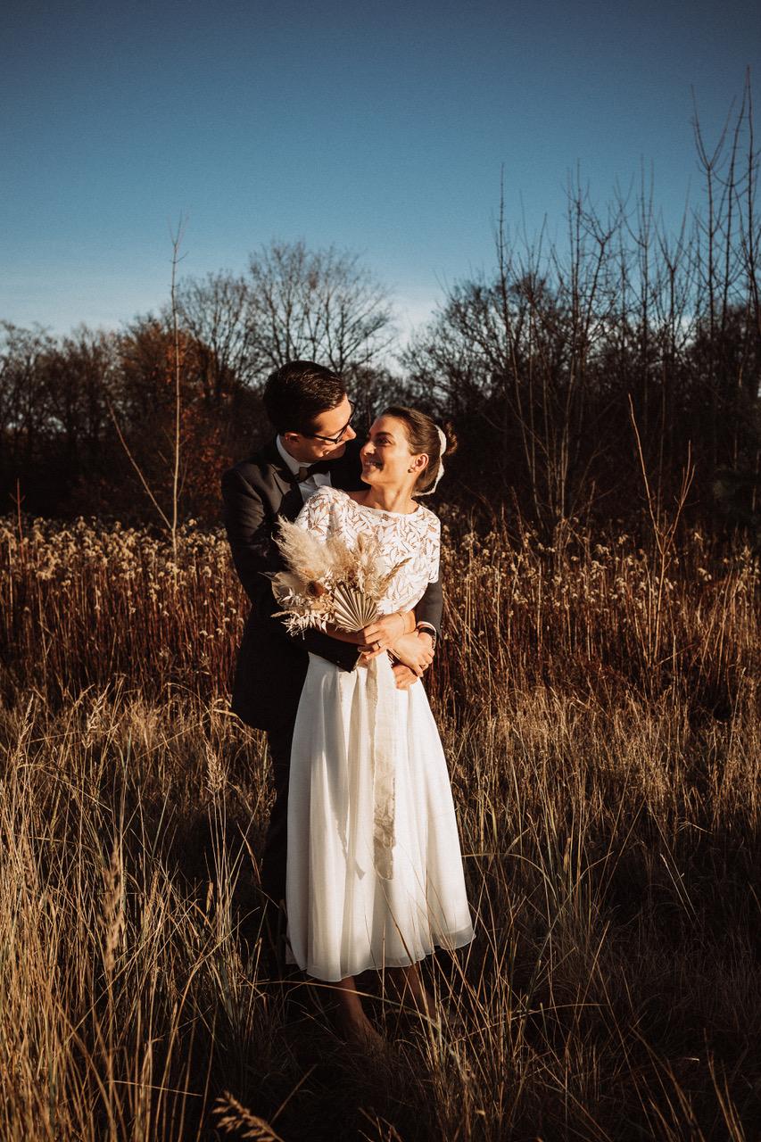 noni Brautmode, Brautpaar sich umarmend in Herbstlandschaft