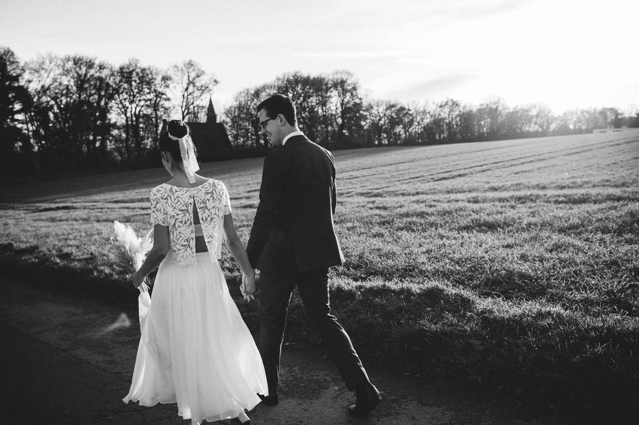 noni Brautmode, Brautpaar händchenhaltend auf Feldweg, Rückenansicht, Schwarz-Weiß-Foto