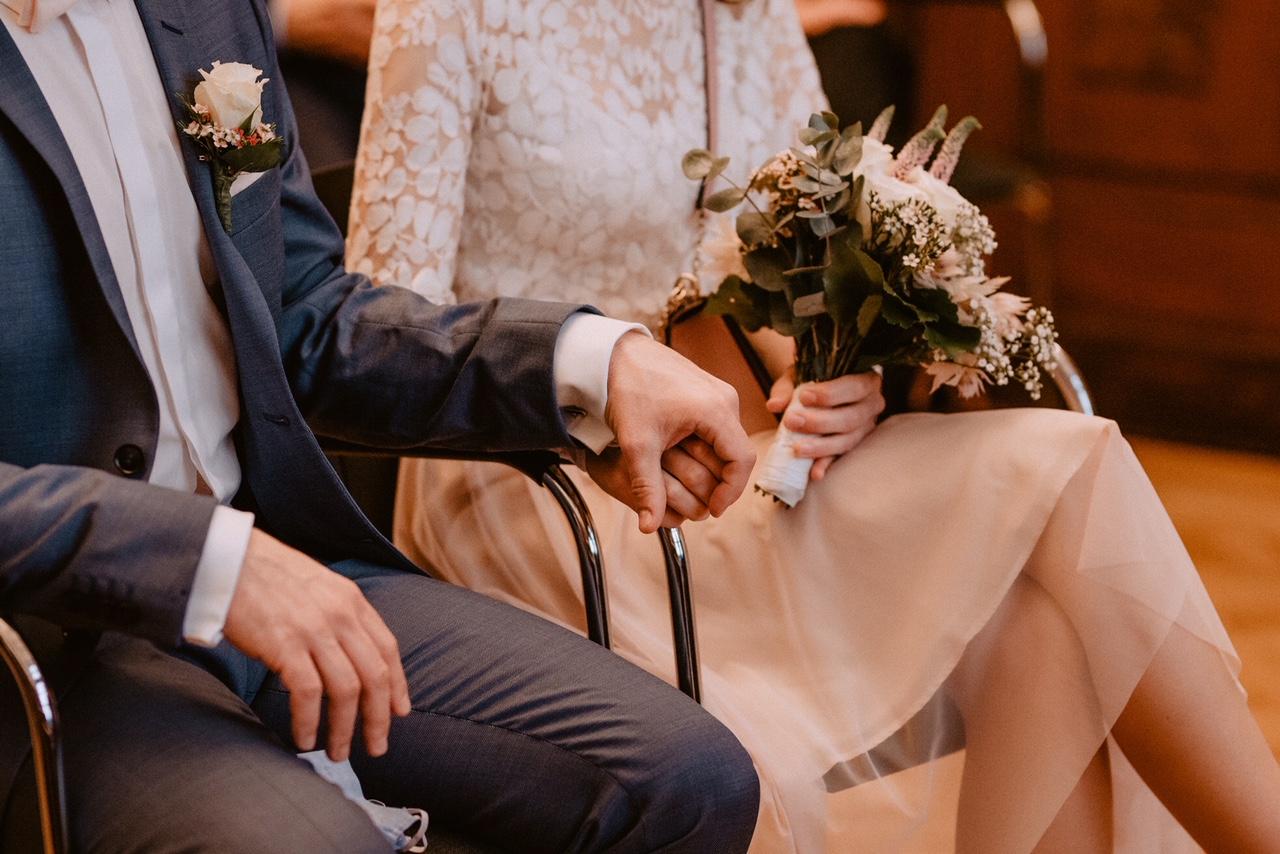 noni Brautmode, Detailaufnahme, Brautpaar auf Stühlen nebeneinander im Standesamt, Nahaufnahme auf Händchenhalten mit Brautstrauss