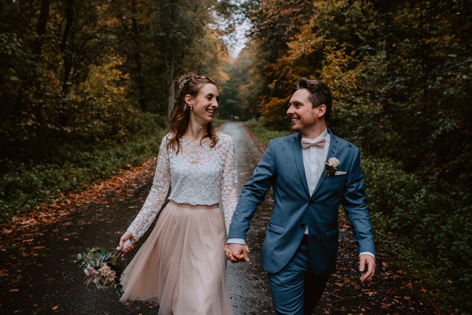 noni Brautmode, Detailaufnahme, Brautpaar vor Herbstwald-Kulisse, händchenhaltend mit Brautstrauss. Bräutigam im blauen Anzug mit Fliege, Braut mit Boho-Brautkleid