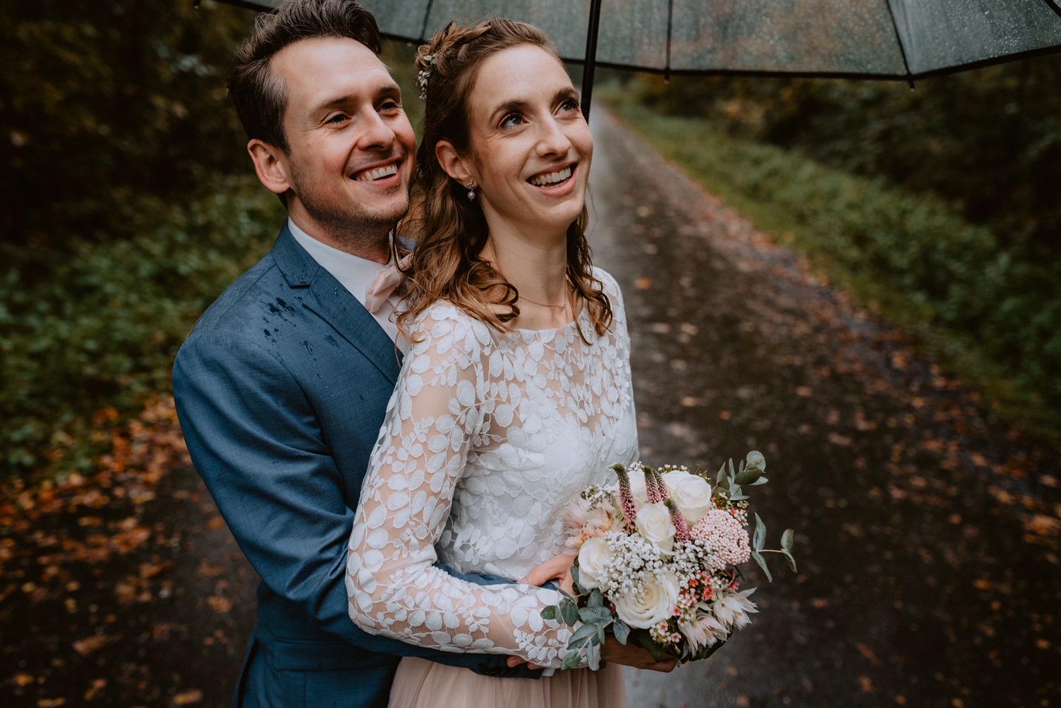 noni Brautmode, Brautpaar sich von hinten umarmend mit Brautstrauss, lächelnd