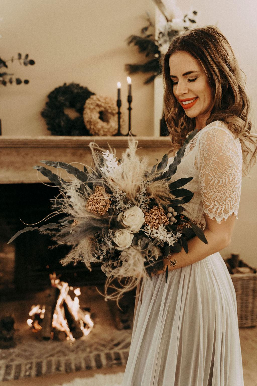noni Brautmode, Styled Shoot. Model mit brünetten offenen, halb-langen Haaren, Blumenstrauss und zweiteiligem Brautkleid im Boho Stil vor Kamin