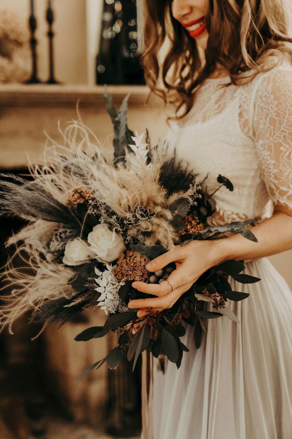 noni Brautmode, Styled Shoot. Model mit brünetten offenen, halb-langen Haaren, Blumenstrauss und zweiteiligem Brautkleid im Boho Stil vor Kamin, Nahaufnahme Brautstrauss