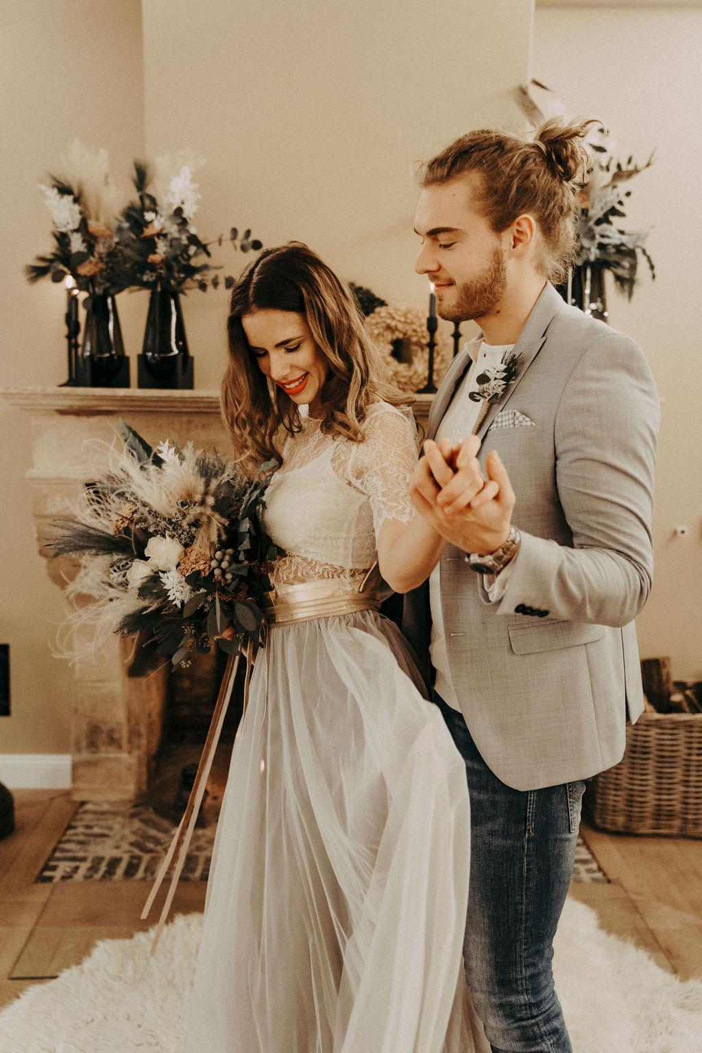 noni Brautmode, Styled Shoot. Model mit brünetten offenen, halb-langen Haaren, Blumenstrauss und zweiteiligem Brautkleid im Boho Stil, Bräutigam mit grauem Sakko