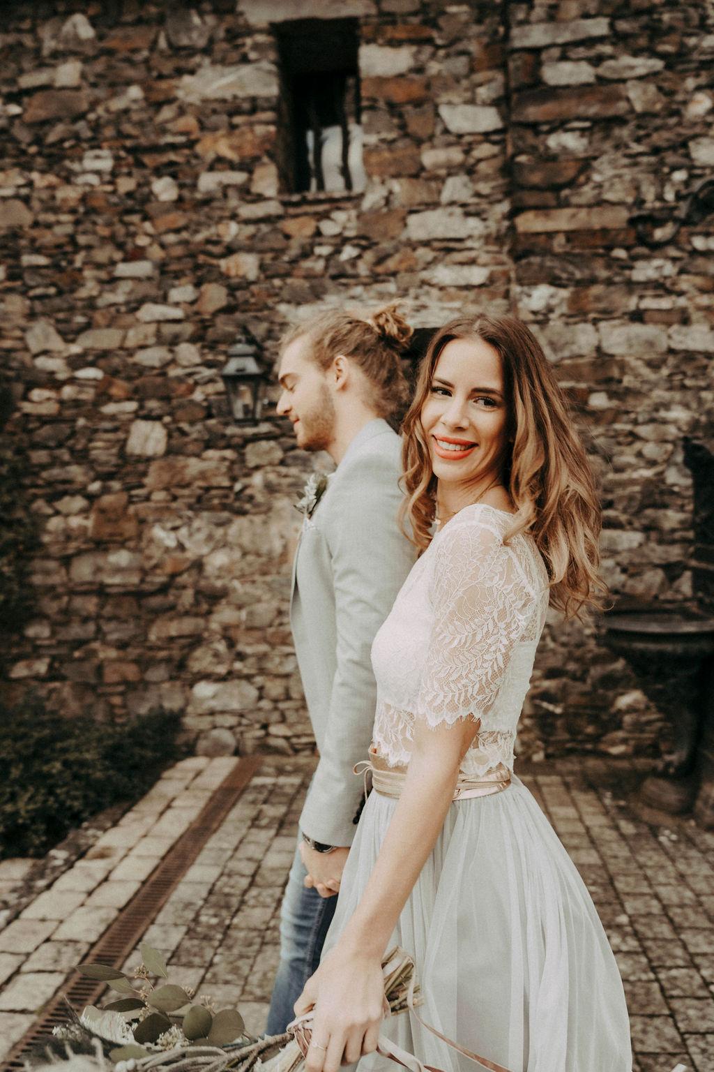 noni Brautmode, Styled Shoot, Brautpaar vor mittelalterlichem Burgtor, Hand in Hand