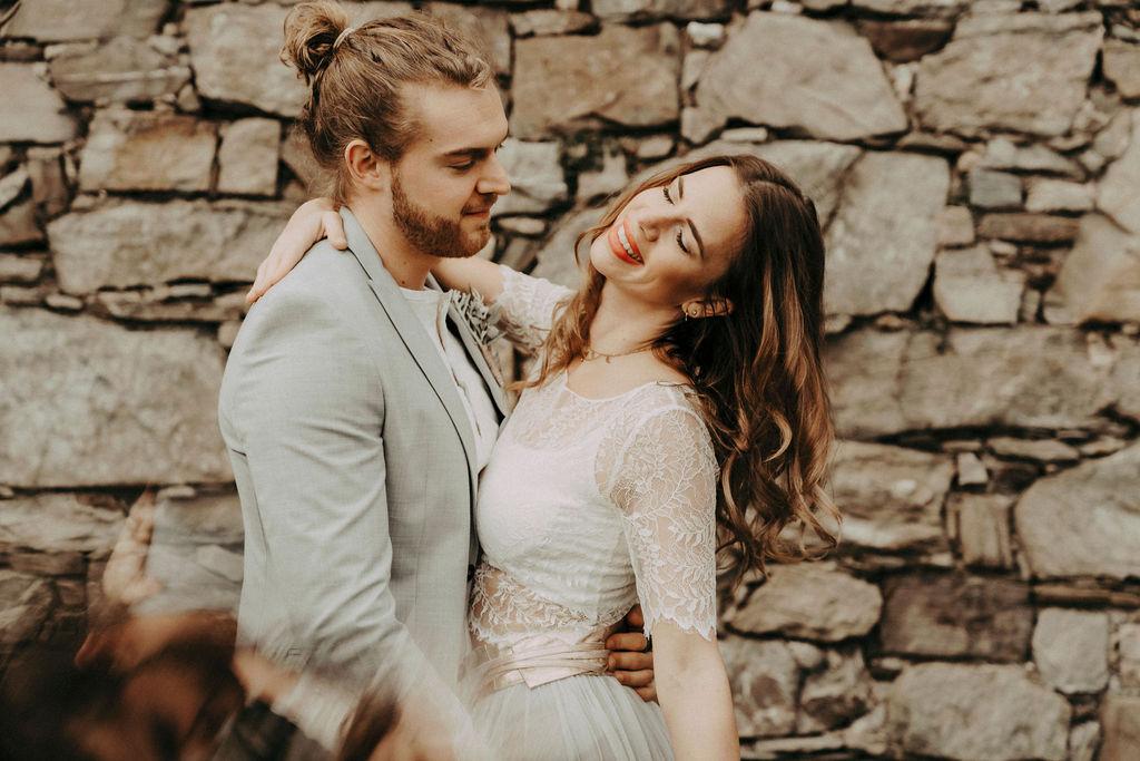 noni Brautmode, Styled Shoot, Brautpaar vor mittelalterlicher Burgmauer in Umarmung