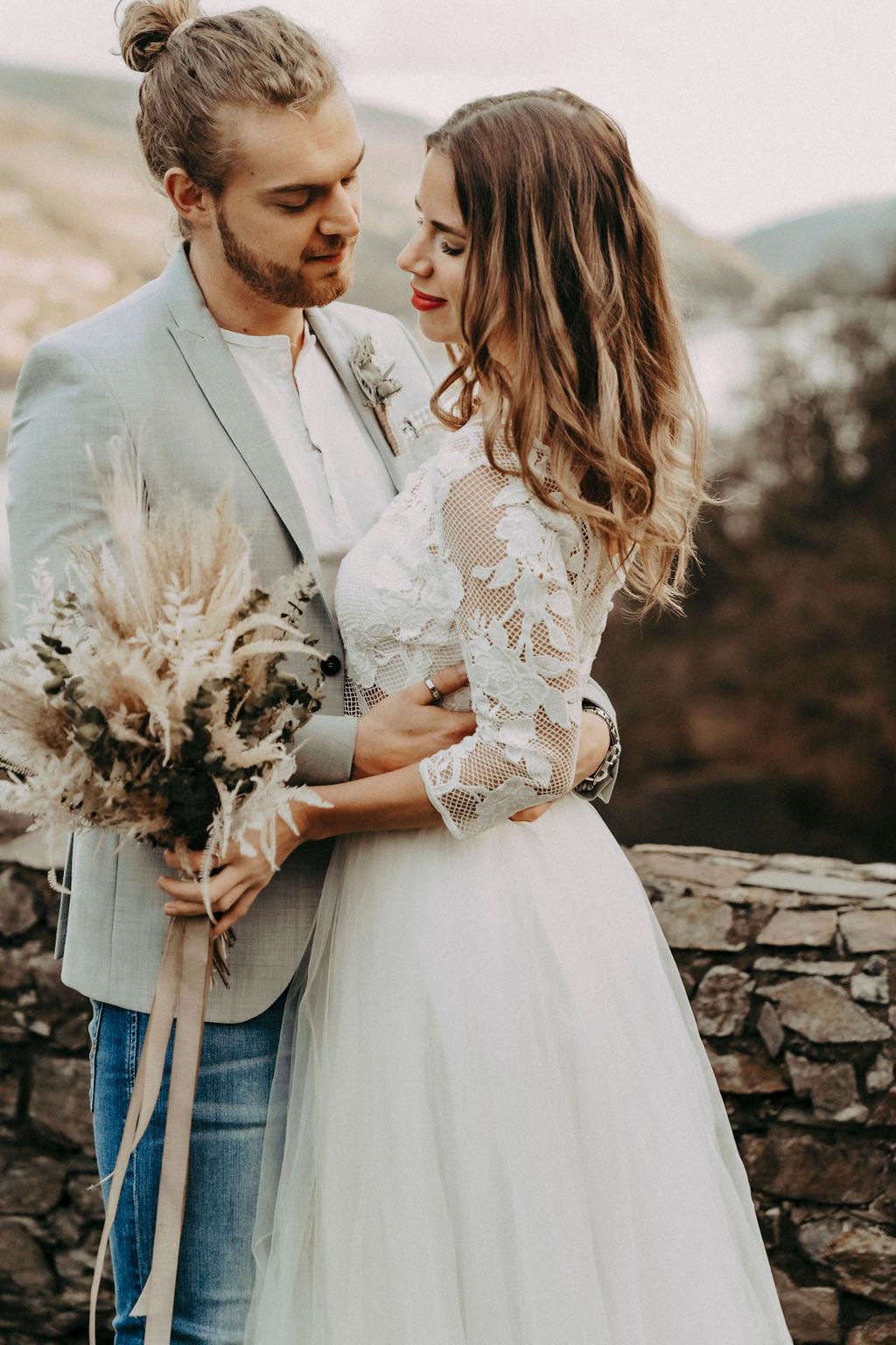 noni Brautmode, Styled Shoot, Brautpaar vor mittelalterliche Kulisse. Bräutigam mit Zopf, Sakko und Bart, Model mit brünetten offenen Haaren und weißem Brautkleid
