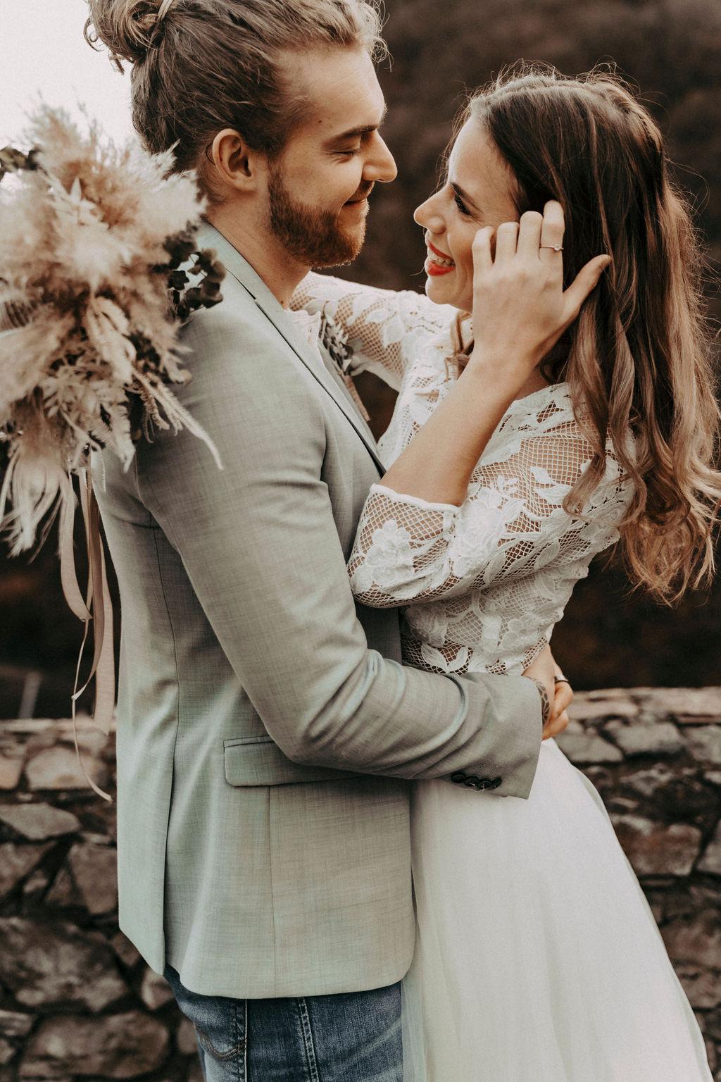 noni Brautmode, Styled Shoot, Brautpaar vor mittelalterliche Kulisse. Bräutigam mit Zopf, Sakko und Bart, Model mit brünetten offenen Haaren und weißem Brautkleid, in Umarmung