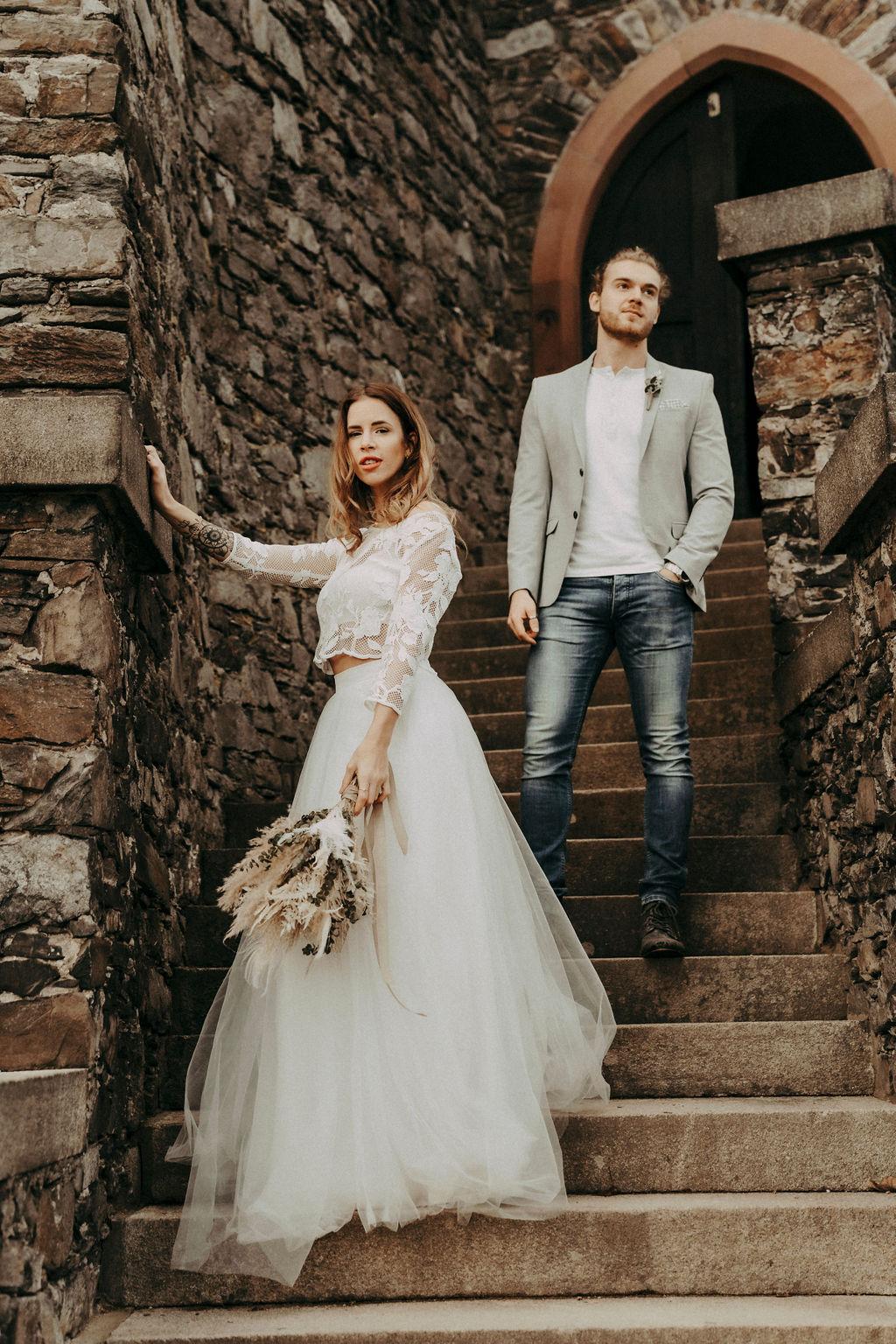 noni Brautmode, Styled Shoot, Brautpaar vor mittelalterliche Kulisse. Bräutigam mit Zopf, Sakko und Bart, Model mit brünetten offenen Haaren und weißem Brautkleid im Boho Stil