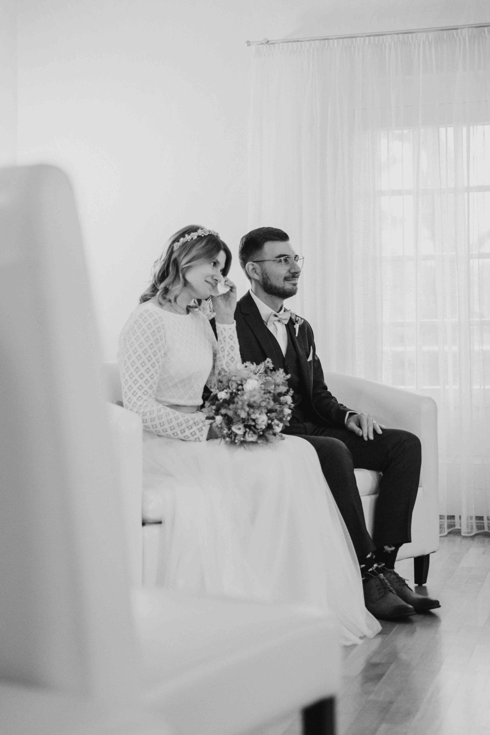 noni Brautmode, Hochzeitsshooting mit Brautpaar im Standesamt auf Stühlen sitzend, schwarz weiss