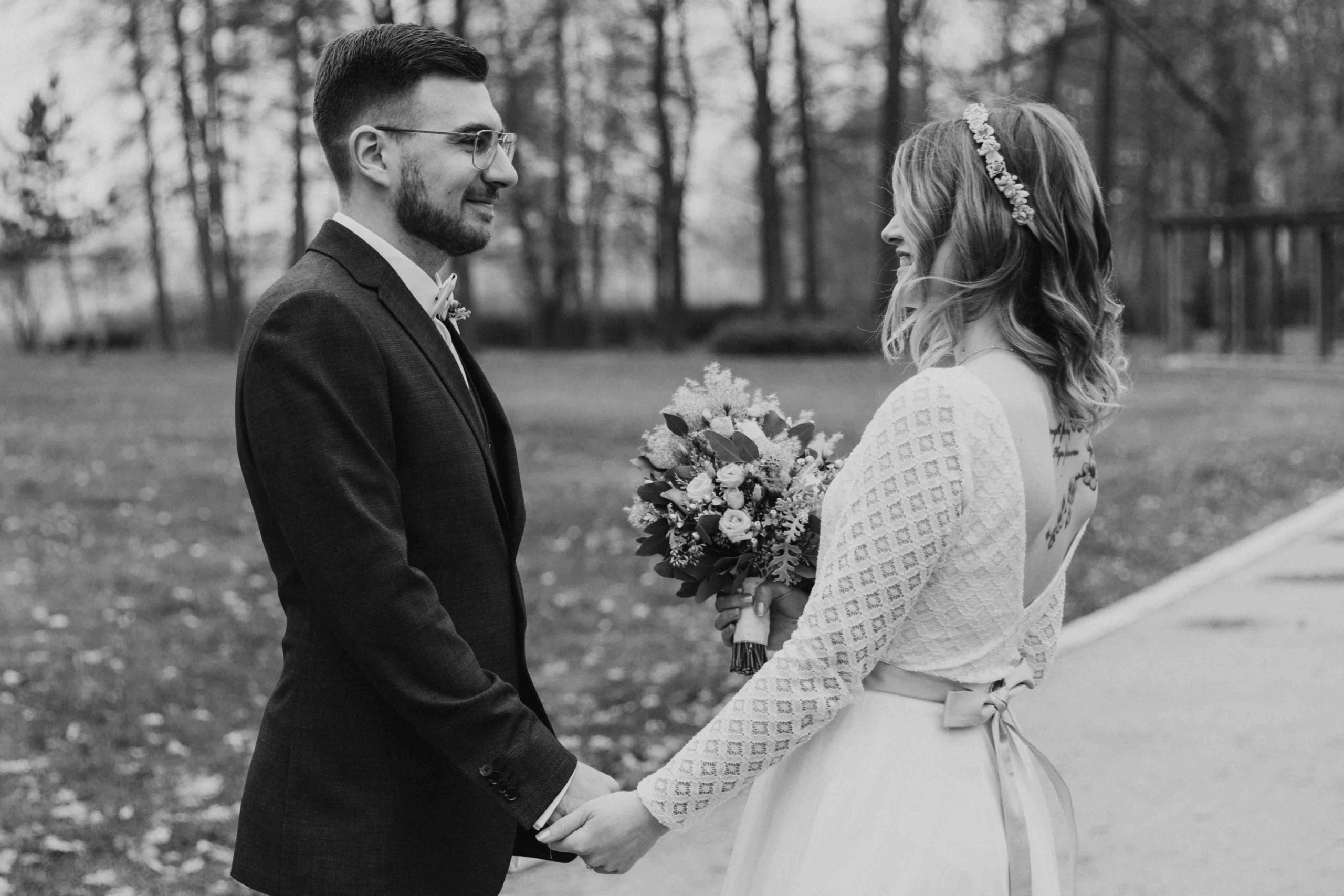 noni Brautmode, Brautpaar händchenhaltend mit Brautstrauss in der Natur. Bräutigam im Anzug, Braut mit rückenfreiem Boho-Brautkleid, Blumenkranz und farbigem Gürtel, schwarz-weiss