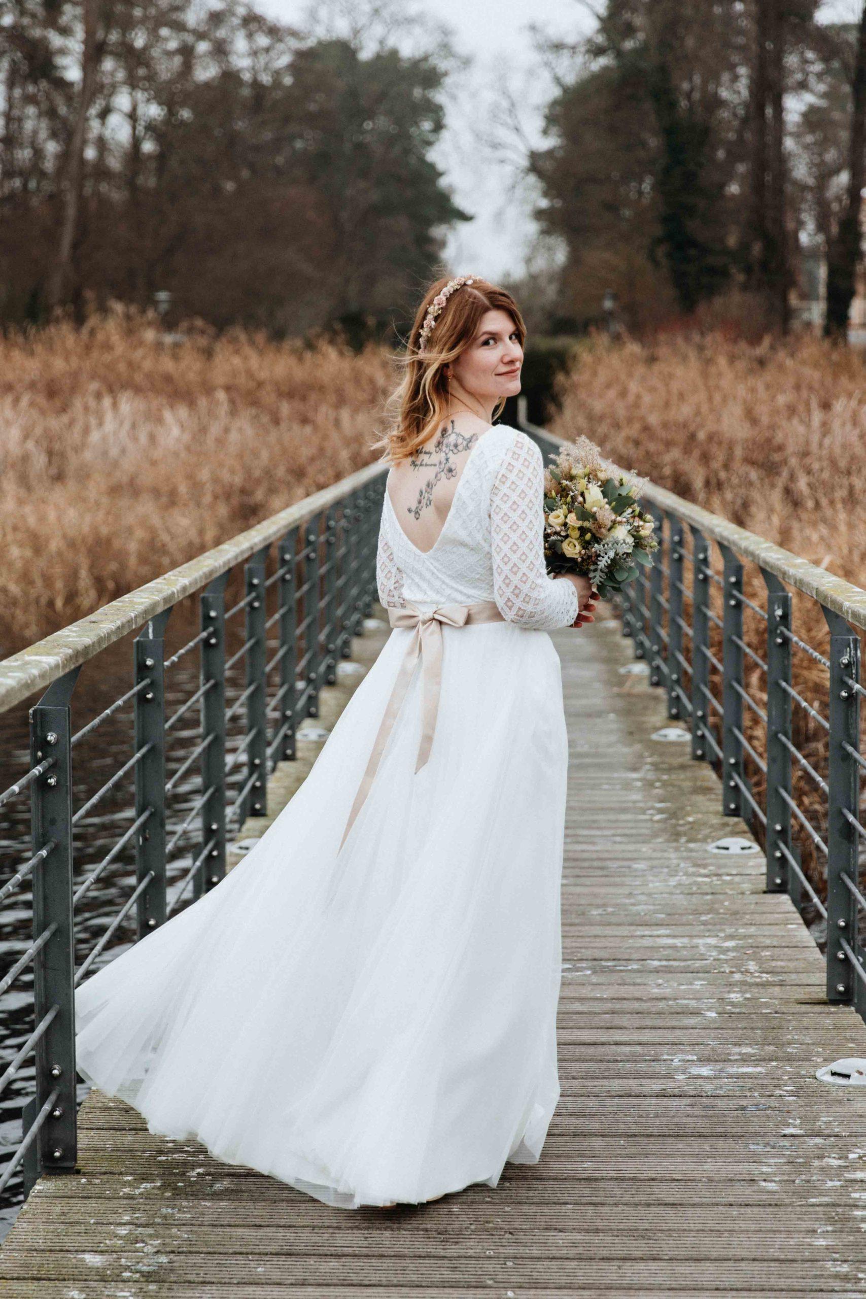 noni Brautmode, Braut in langem, weißen Brautkleid mit Rückenausschnitt auf Steg