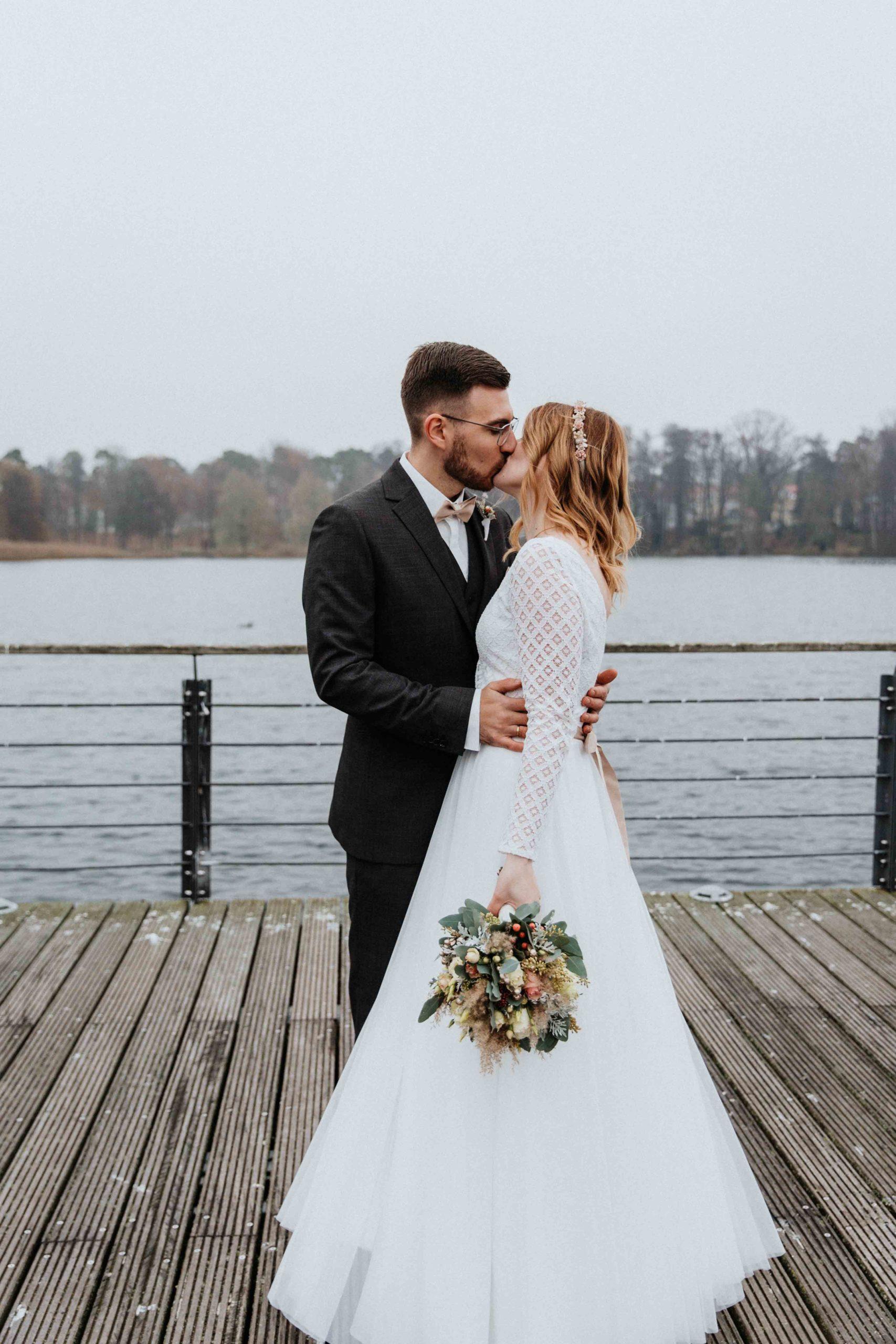 noni Brautmode, Brautpaar sich umarmend und küssend auf Steg