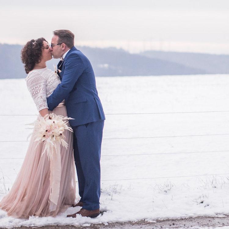 Brautpaar küssend vor Schneelandschaft
