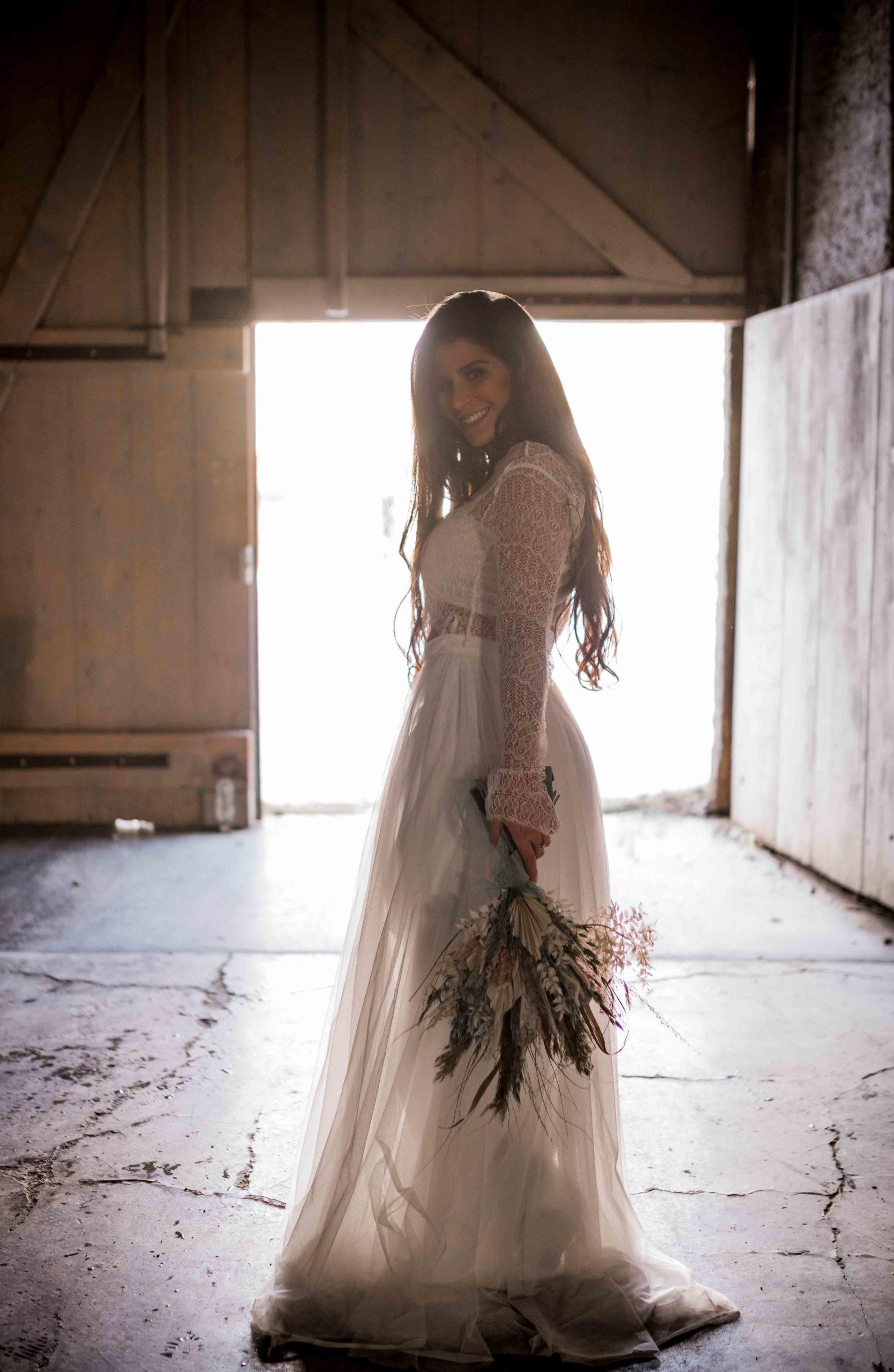 noni Brautmode, Styled Shoot, Model mit langem Kleid, Seitenasnsicht, Strauss haltend und lachend