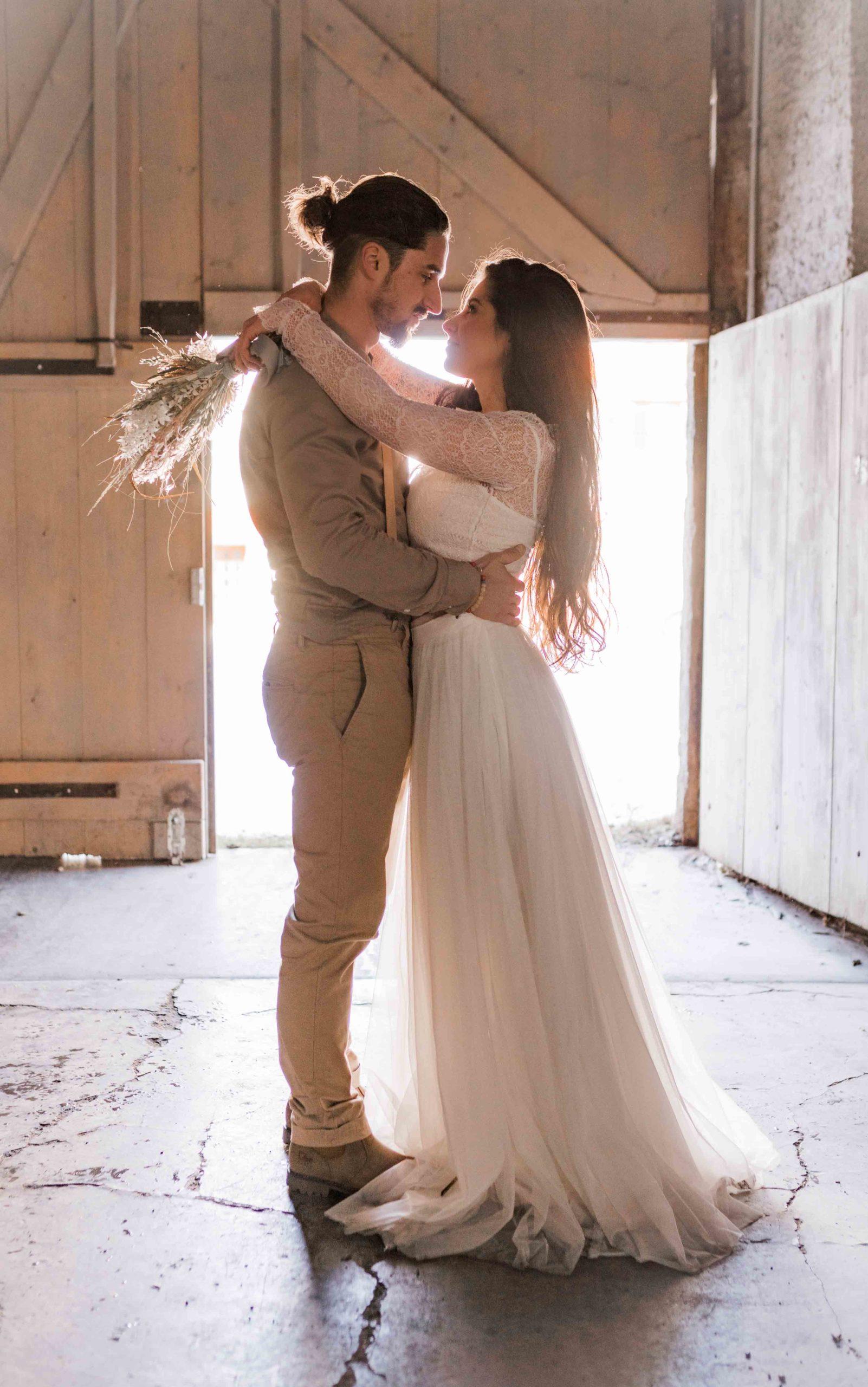 noni Brautmode, Styled Shoot, Model mit langem Kleid, Seitenasnsicht, Strauss haltend, Bräutigam umarmend
