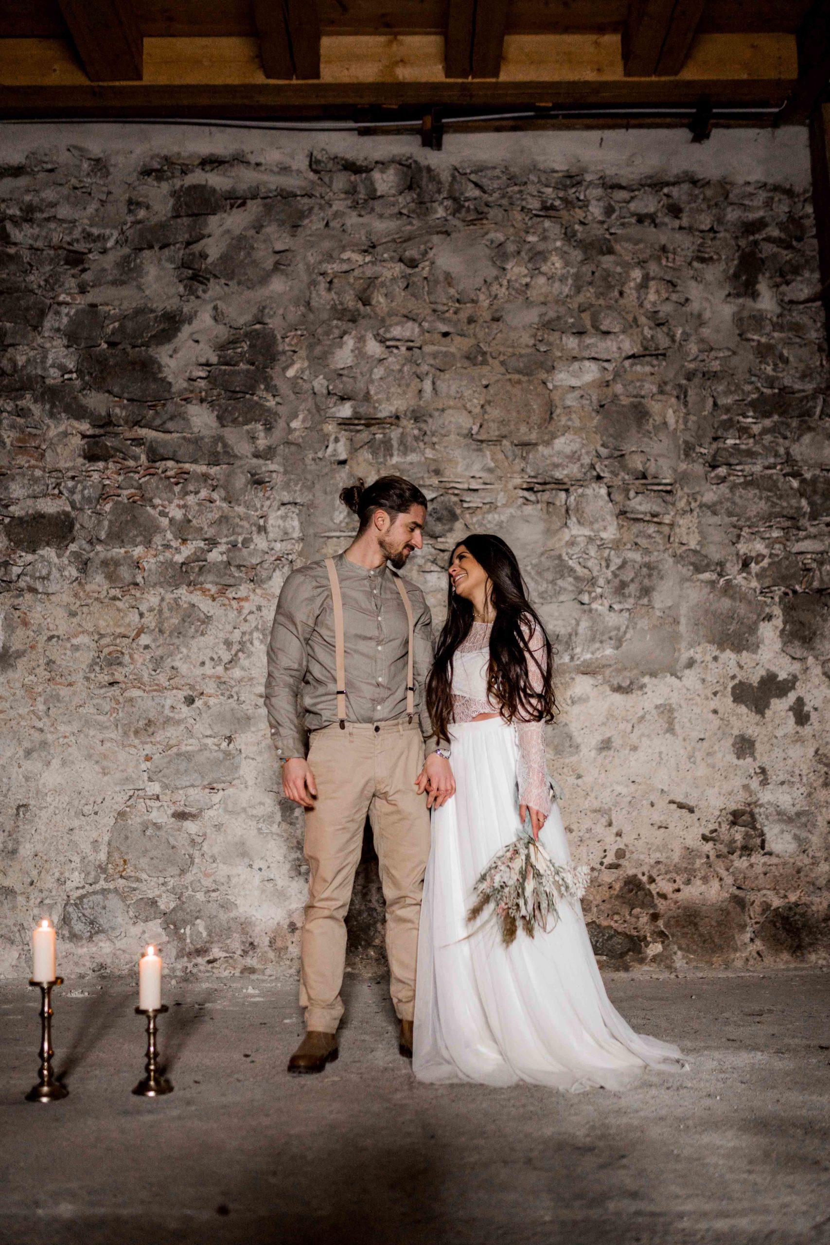 noni Brautmode, Styled Shoot, Brautpaar händchenhaltend vor Steinwand
