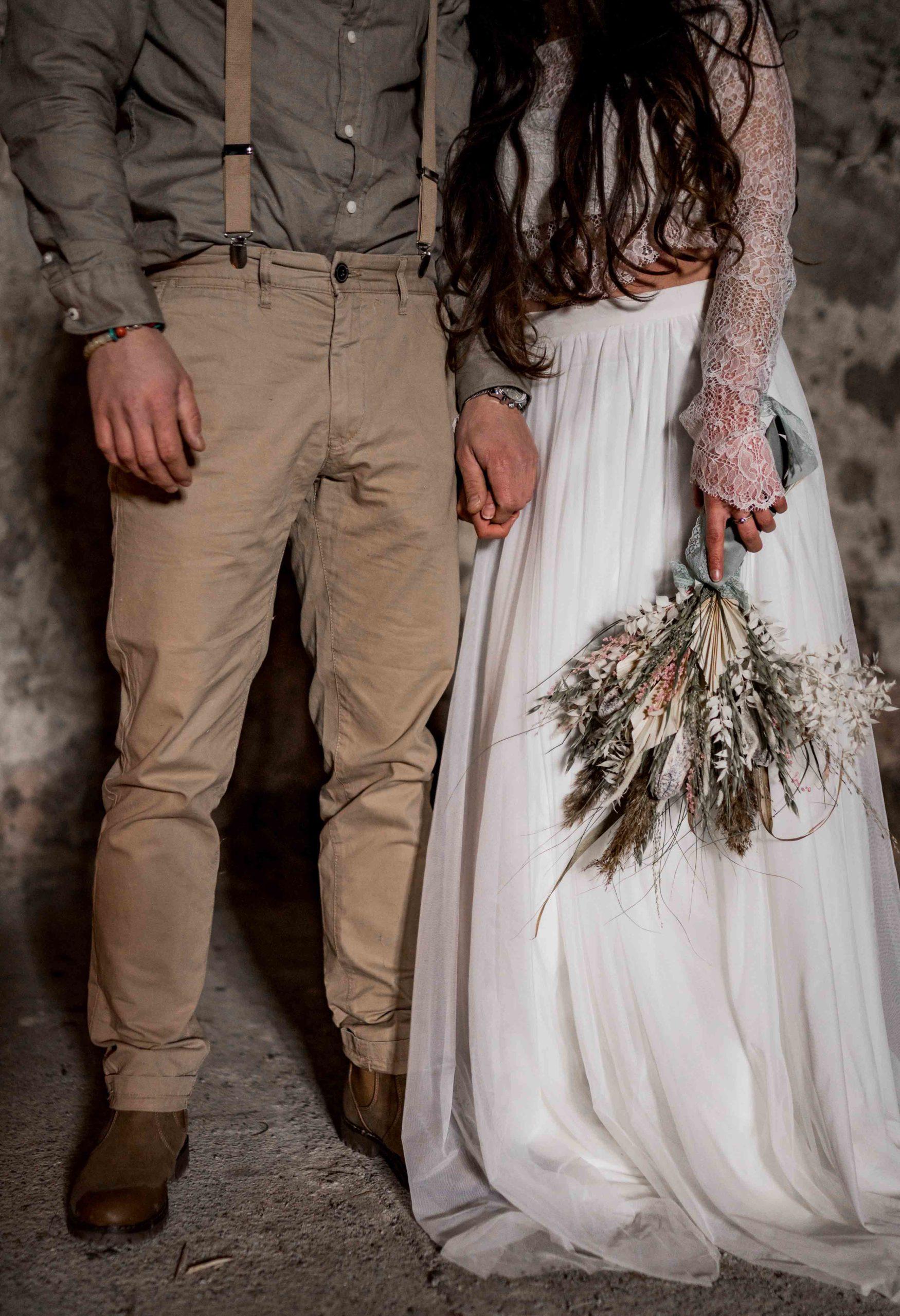 noni Brautmode, Styled Shoot, Brautpaar händchenhaltend vor Steinwand, Nahaufnahme von Strauss, Rock und Anzugshose