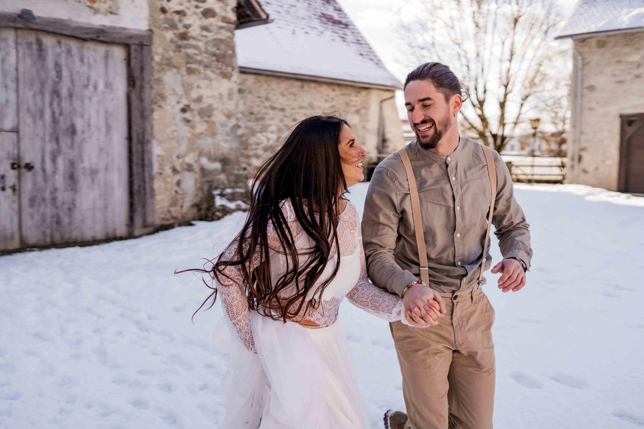 noni Brautmode, Styled Shoot, Brautpaar händchenhaltend und lachend im Schnee