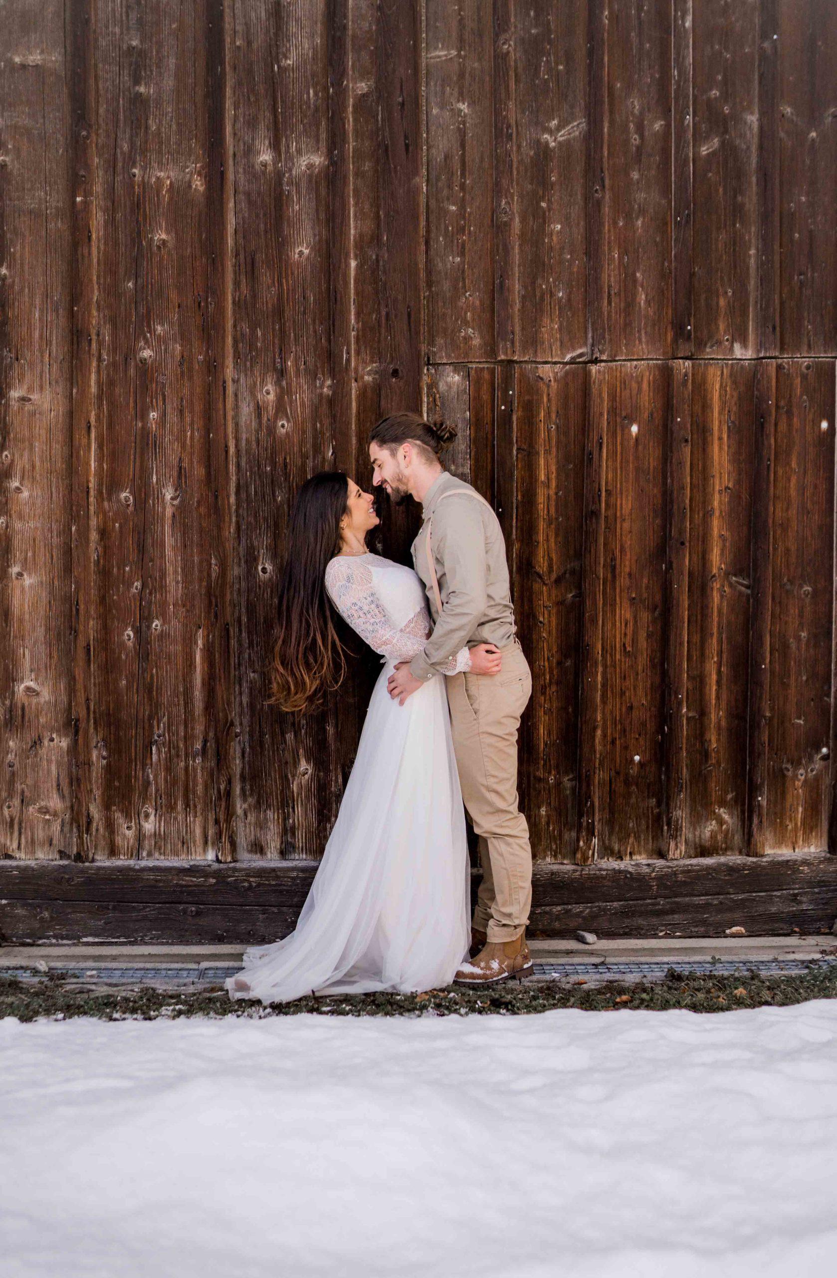 noni Brautmode, Styled Shoot, Brautpaar händchenhaltend und lachend im Schnee vor Holzfassade