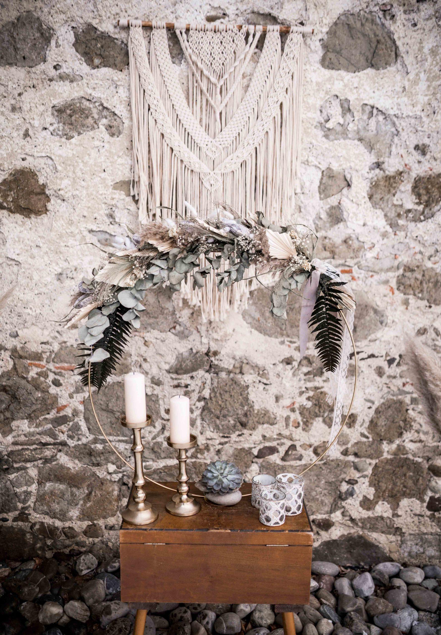 noni Brautmode, Styled Shoot, Dekoration aus Trockenblumen, Kerzenständern und Teelichten, Wandbehang aus Macramé an Steinwand