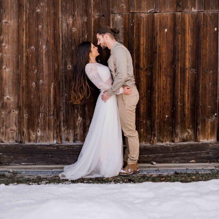 noni Brautmode Styled Shoot mit Model-Paar lachend vor Holztor im Schnee