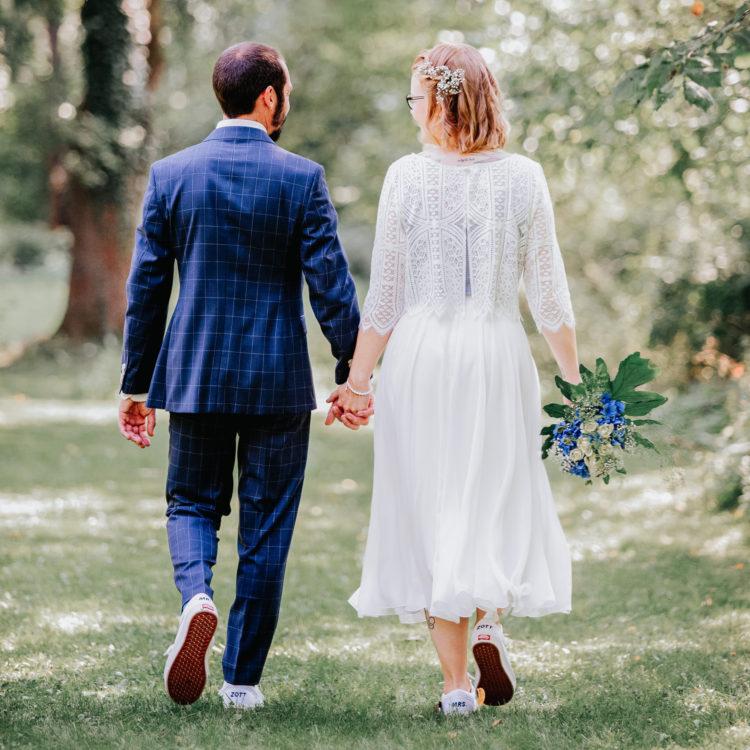 Brautpaar im Grünne, händchenhaltend. Bräutigam in blauem Anzug, Braut in elfenbeinfarbenem Midi-Kleid mit blauem Bluemnstrauss, beide in Sneakers im Partnerlook