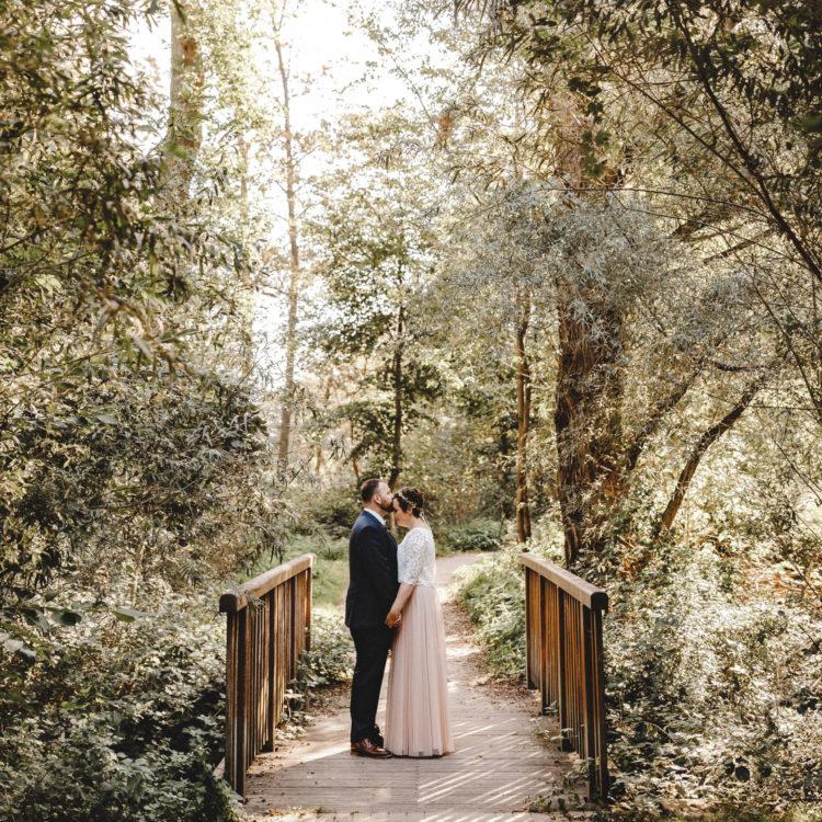 Brautpaar auf Brücke vor Waldkulisse