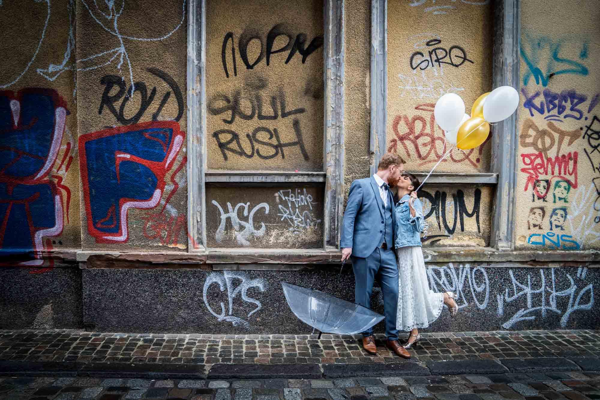 Brautpaar mit Regenschirmen vor bunter Graffiti-Mauer. Bräutigam mit blauem Dreiteiler und Fliege, Braut mit Jeansjacke und Midi-Kleid in Ivory