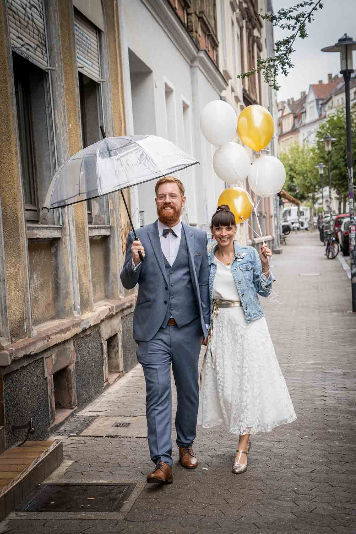 Brautpaar mit ReBrautpaar auf Strasse, Hand in Hand. Bräutigam mit blauem Dreiteiler und Fliege und Regenschirm, Braut mit Jeansjacke und Midi-Kleid in Ivory, Luftballons haltend