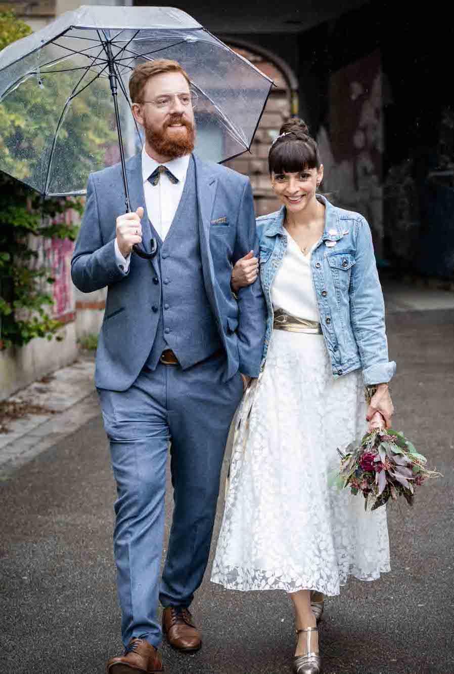 Brautpaar mit Brautpaar auf Strasse, Bräutigam mit blauem Dreiteiler und Fliege und Regenschirm, Braut mit Jeansjacke und Midi-Kleid in Ivory, Brautstrauss haltend