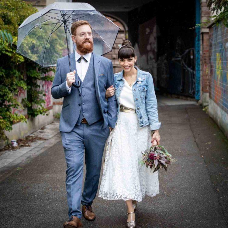 noni Brautmode, Brautpaar lachend unter Regenschirm