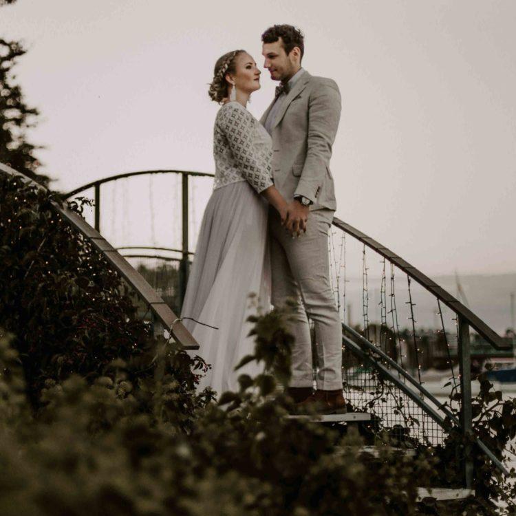noni Brautmode, Styled Shoot. Brautpaar auf Brücke händchenhaltend