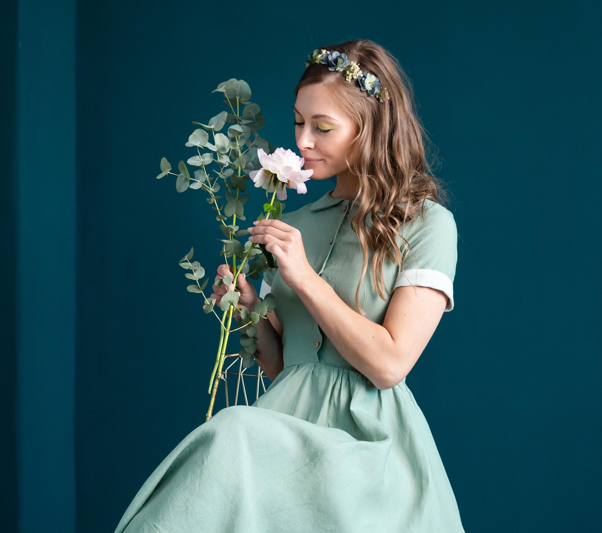 Frau mit grünem Leinenkleid und Blumen