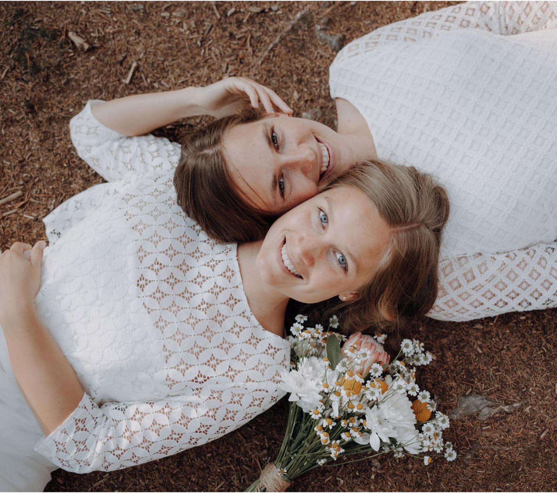 Zwei Frauen liegen auf einer Blumenwiese