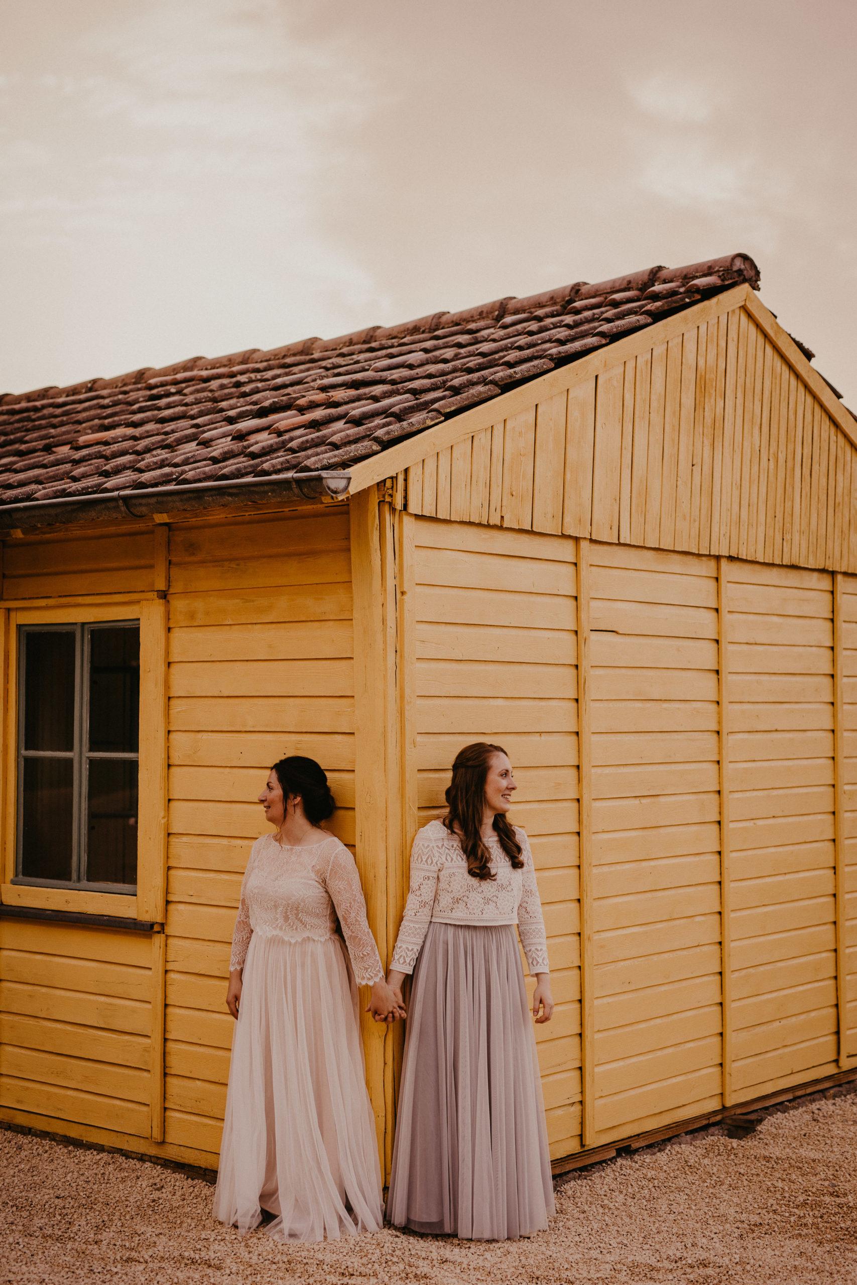 Lesbisches Brautpaar vor Haus