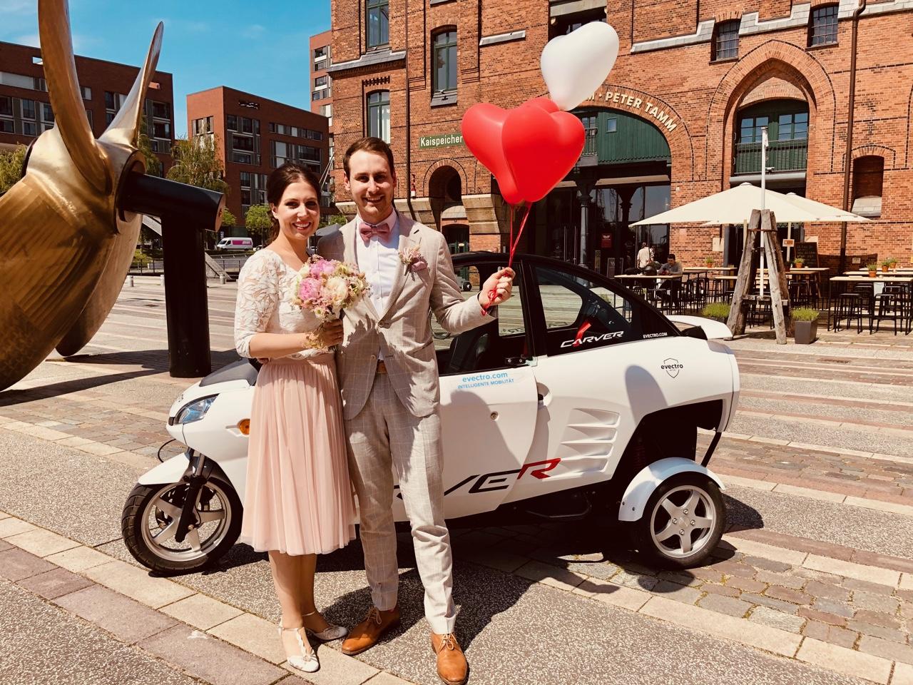 Brautpaar steht vor Auto