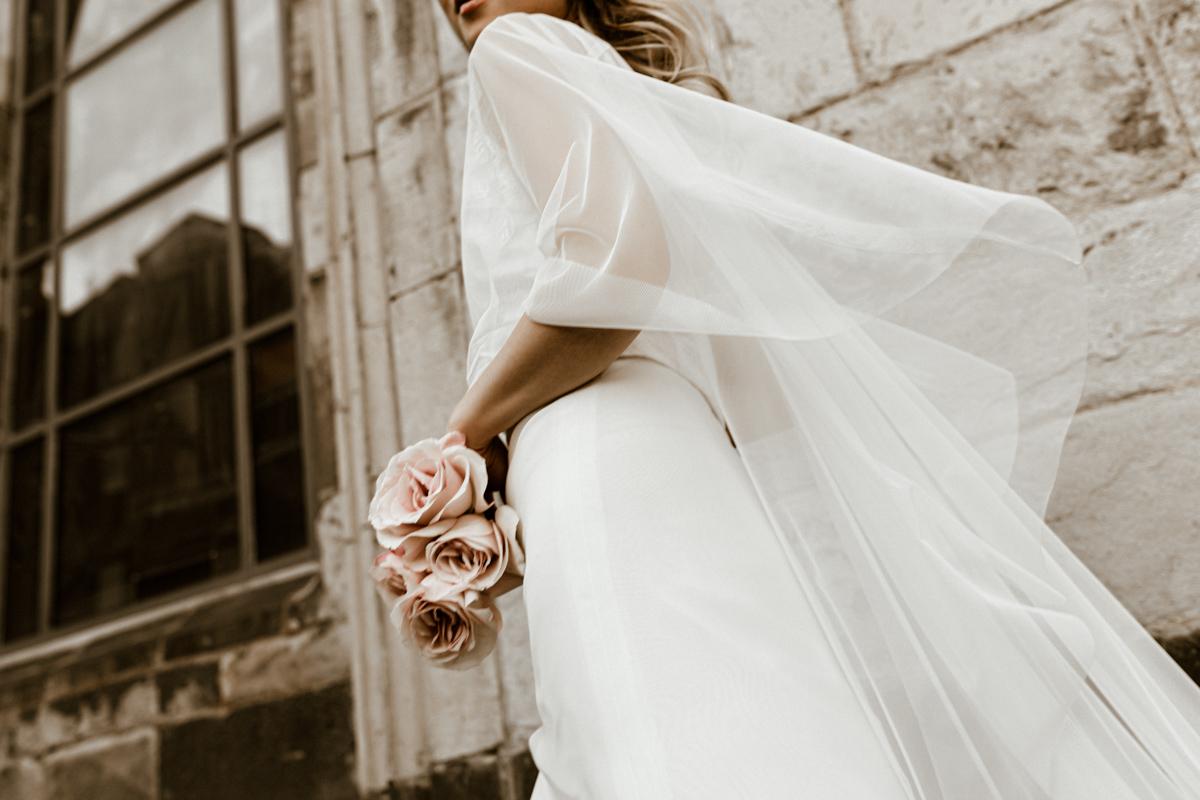 Querformat: Blonde Frau mit Schleppen-Tüllcape und langem Brautkleid aus Efeu-Tüll und Rock, Nahaufnahme von unten