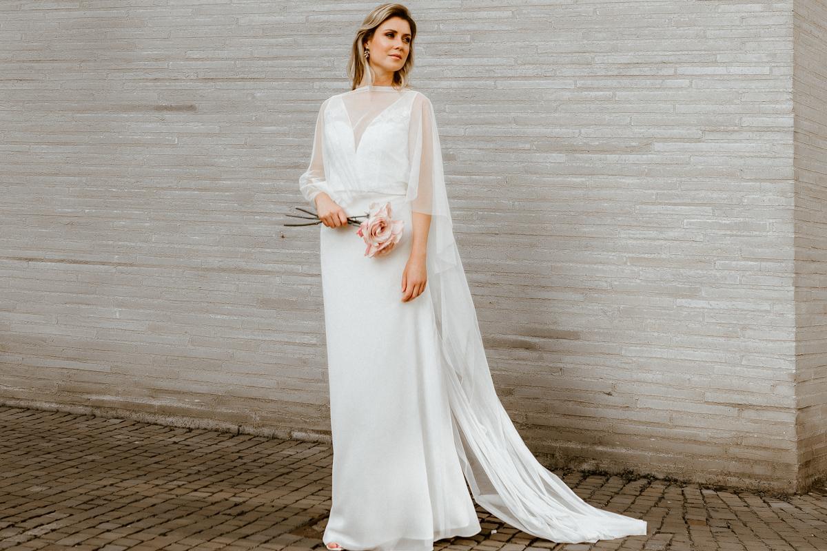 Querformat: Blonde Frau mit Schleppen-Tüllcape und langem Brautkleid aus Efeu-Tüll und Rock