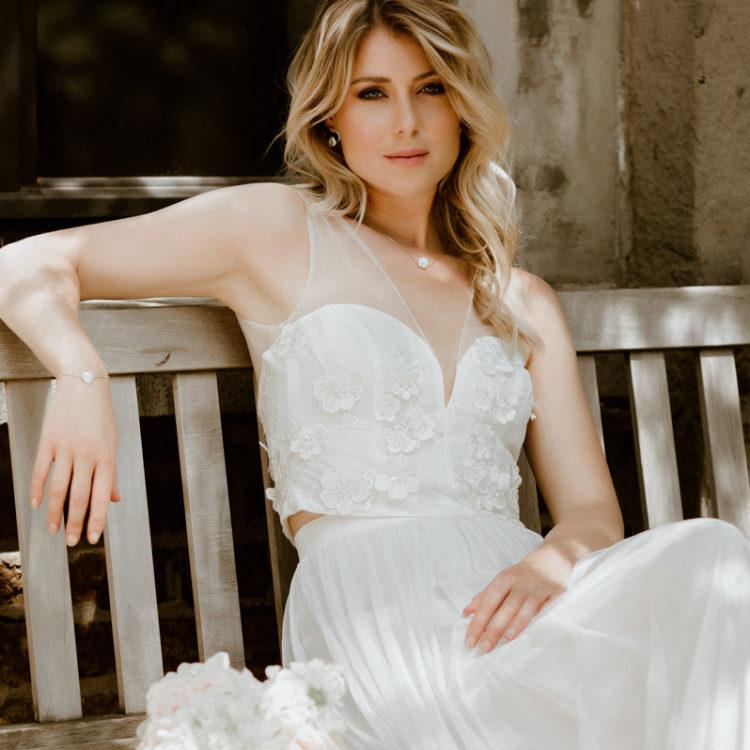 Quadrat-Format: Blonde Frau mit ärmellosem Tülltop mit V-Ausschnitt und Blütenstickerei zu langem Tüllrock in Ivory, sitzend auf Holzbank in Sonne