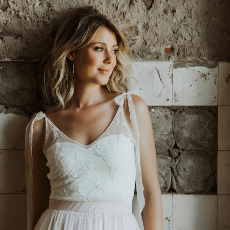 Quadrat-Format: Blonde Frau mit ärmellosem Body aus Tüll in Ivory mit Blumenmuster und fliederfarbenem Tüllrock, vor Steinwand lehnend