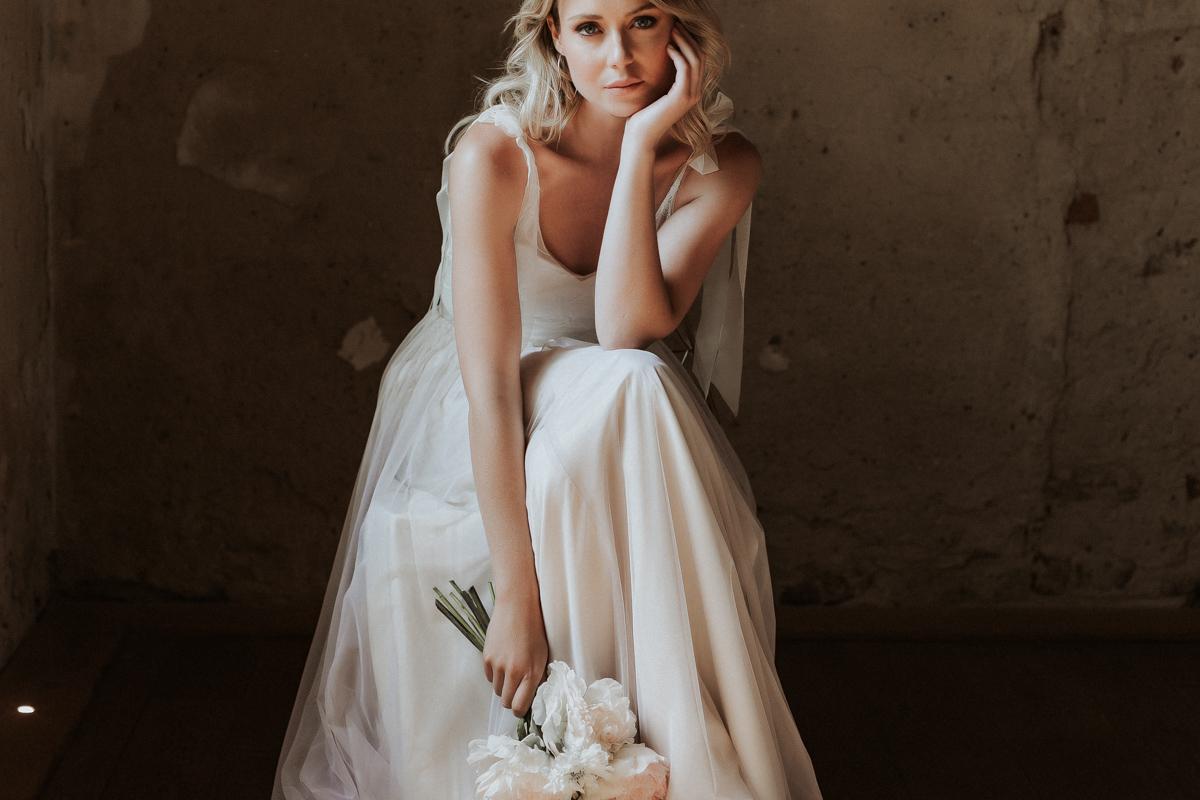 Querformat: Blonde Frau mit ärmellosem Body aus Tüll in Ivory mit Blumenmuster und Tüllrock, Vorderansicht