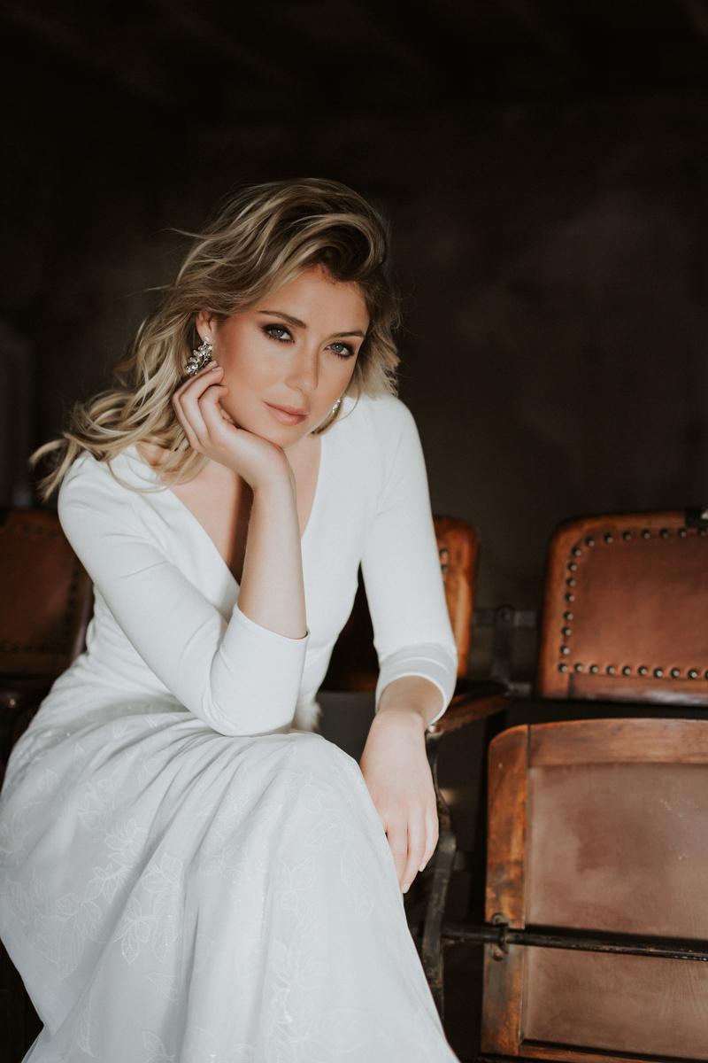 Hochformat: Blonde Frau mit V-Ausschnitt-Top in Ivory und langem Rock mit Efeu-Muster, sitzend